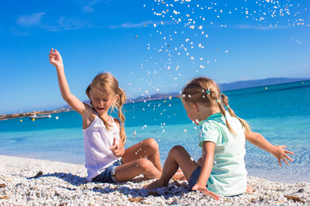 have fun: Adorable little girls have fun on white beach during vacation