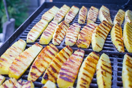 grill: Fried pineapples on grill outdoor Stock Photo