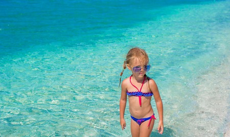 girl alone: Little girl having fun on tropical beach with turquoise ocean water Stock Photo