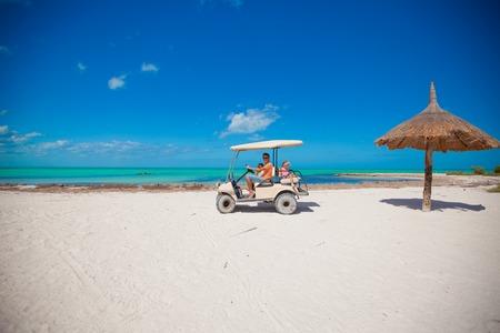 golf cart: Dad and his little girls driving golf cart on tropical beach