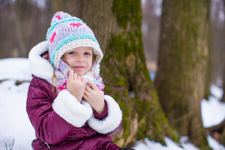 Portrait of little happy girl in the snow sunny winter day photo