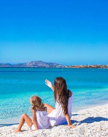 tropical island: Young happy mother and adorable daughter having fun at exotic beach on sunny day