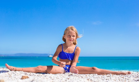 Happy little sporty girl on white tropical beach Stock Photo