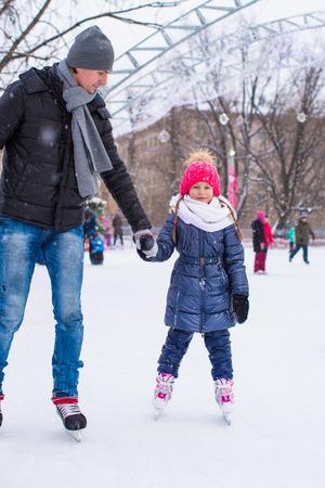patinaje sobre hielo: Ni�a adorable y pap� feliz en pista de patinaje al aire libre