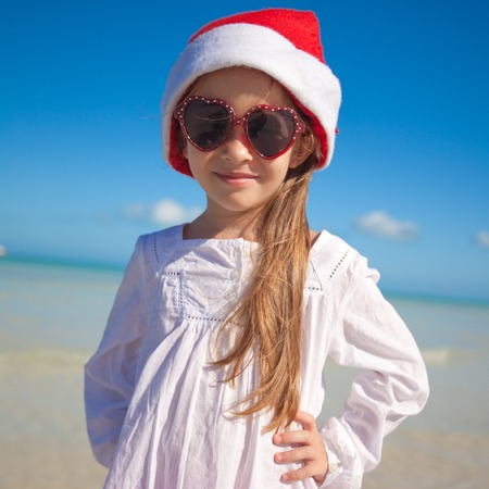 Little adorable girl in red Santa hat at tropical beach photo