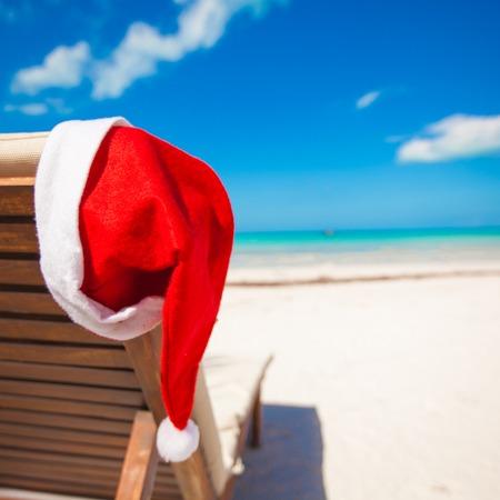 longue: Red santa hat on chair longue at tropical caribbean beach Stock Photo