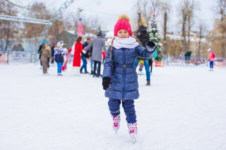 ice rink: Cute little girl skating on the ice rink outdoors Stock Photo