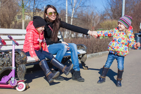 Little cute girls and young mother have fun outdoors photo
