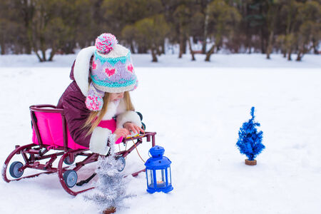 Little cute girl warms her hands on candle in blue lantern in winter time photo