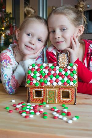 ni�os ayudando: Las ni�as adorables que decoran la casa de pan de jengibre para la Navidad Foto de archivo