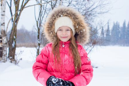 Adorable little girl outdoors on winter snow day photo