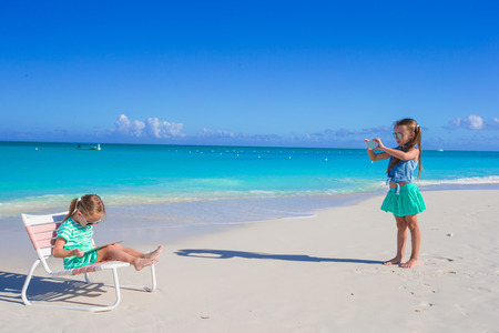 Little girl photographed her cute sister with a laptop photo