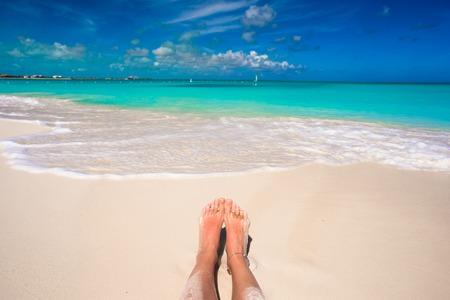footsie: Close up of female feet on white sandy beach