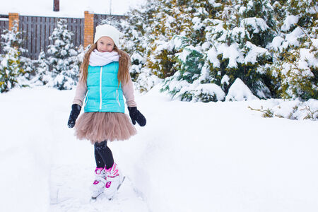 Adorable little girl skating in winter snow day outdoors photo