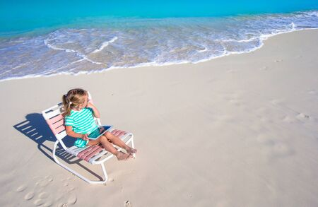 girl with laptop: Little adorable girl with laptop on beach during summer vacation