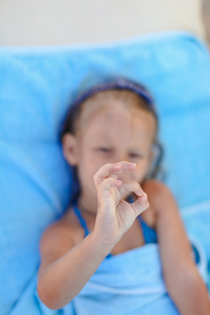 Little girl showing thumbs up outdoor photo