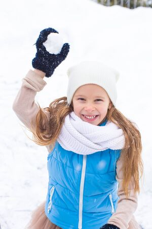 snowballs: Adorable little girl playing snowballs in winter outdoors Stock Photo