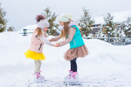 Adorable little girls skating on ice rink outdoors in winter snow day photo