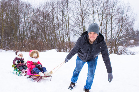 to go sledding: Young father with little daughters sledding in winter outdoors