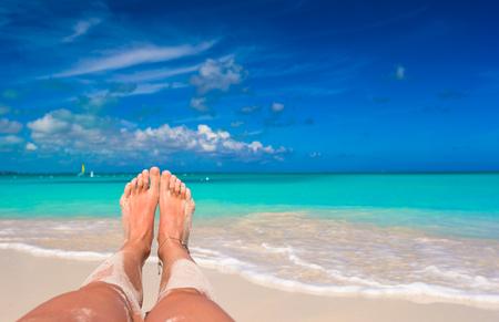 mujer ba�andose: Pies femeninos en la playa de arena blanca