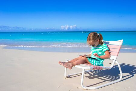 carribean: Little girl with laptop on beach during summer vacation