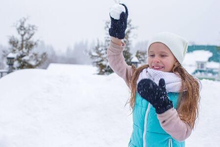 neve palle: Poco bella ragazza che gioca a palle di neve nevoso inverno giorno Archivio Fotografico