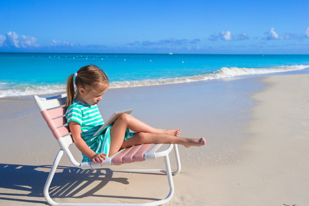 little girl beach: Little adorable girl with laptop on beach during summer vacation