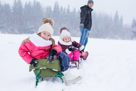 to go sledding: Happy family in winter outdoors