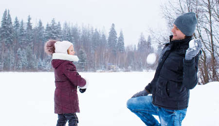 snowballs: Happy family playing snowballs in winter snowy day