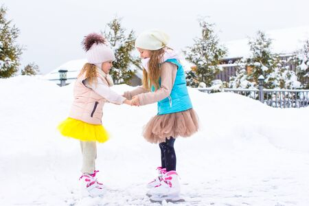 Little girls skating on ice rink outdoors in winter snow day photo