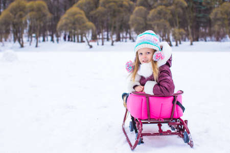 Adorable little happy girl have fun in winter snowy day photo