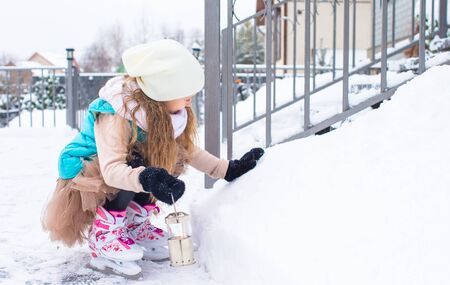 Adorable little girl skating in winter snow day photo