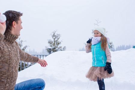snowballs: Buon padre e bambina giocare a palle di neve in inverno giorno nevoso
