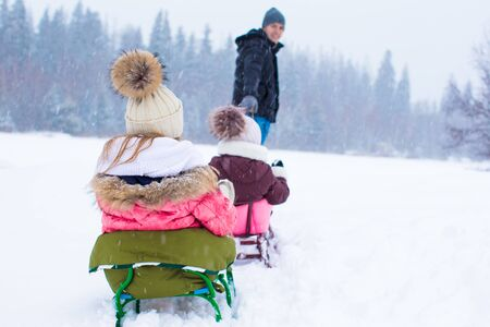 to go sledding: Happy family sledding in winter outdoors