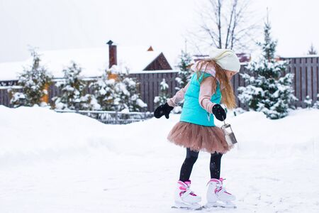 Adorable little girl skating in winter snowy day outdoors photo