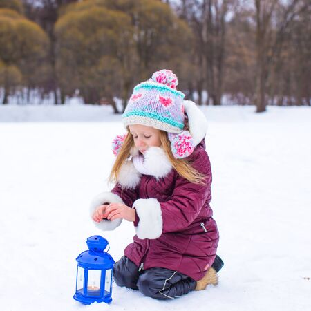 Little girl warms hands on candle in lantern outdoors photo