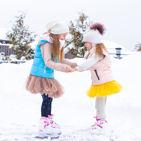Adorable little girls skating on ice rink in winter snow day photo