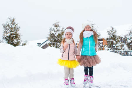 Little happy girls skating outdoors in winter snow day photo