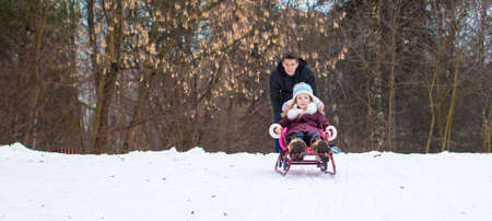 Little girl and happy father sledding in winter snowy day photo