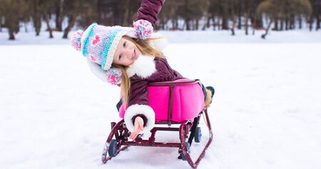 Adorable little happy girl sledding in winter snowy day photo