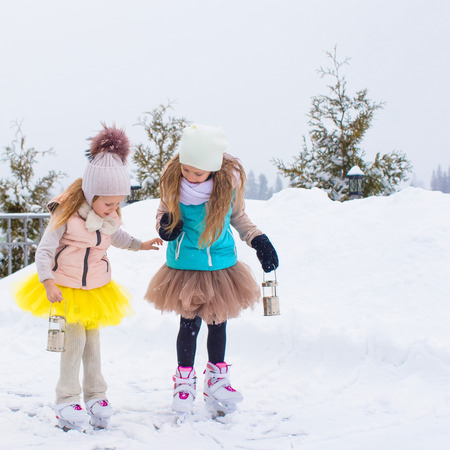 Adorable little girls skating on ice rink outdoors photo