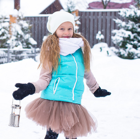 Adorable little girl holding Christmas lantern outdoors on beautiful winter snow day photo