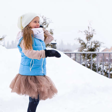 Adorable little girl playing snowballs in winter outdoors photo