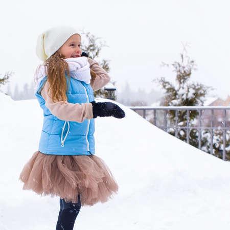 snowballs: Bambina adorabile che gioca le palle di neve in inverno all'aperto