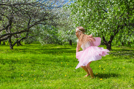 Adorable little girl have fun in blossoming apple tree garden photo
