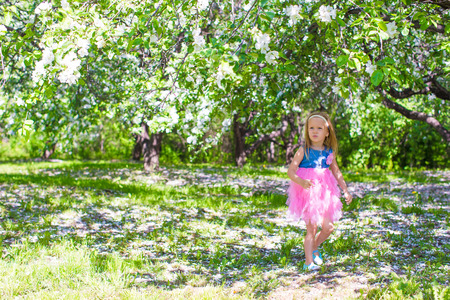 girl apple: Adorable little girl have fun in blossoming apple tree garden at may