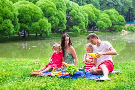 picnicking: Happy young family picnicking outdoors