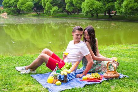 picnicking: Young happy couple picnicking outdoors