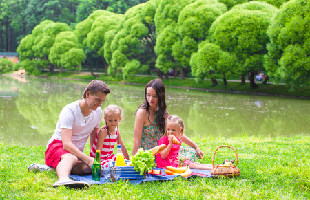 picnicking: Happy parents and two kids picnicking outdoors