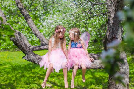 Kleine schattige meisjes zitten op de bloeiende boom in apple tuin Stockfoto